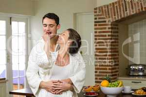 Man embracing while woman feeding strawberry to him