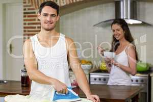 Portrait of man ironing a shirt in kitchen