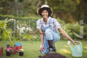 Smiling woman crouching in the garden