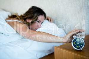 woman reaching to turn off her alarm clock