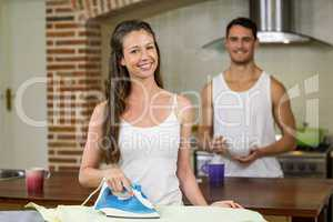 Portrait of woman ironing a shirt in kitchen
