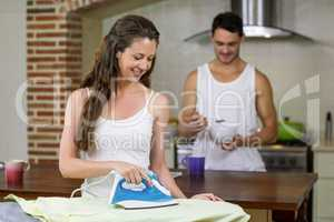 Woman ironing a shirt in kitchen