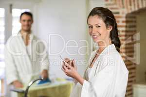 Beautiful woman in bathrobe typing a text message on smartphone