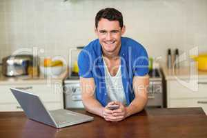 young man leaning on kitchen worktop