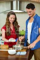 young couple preparing batter in pan