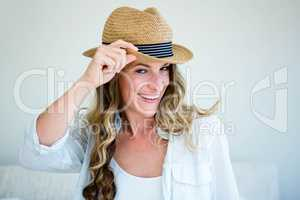 woman wearing a straw fedora smiling and looking away