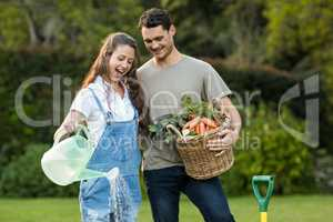 Woman watering a plants while man holding basket of vegetables