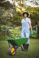 Smiling woman pushing wheelbarrow