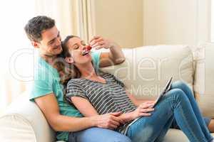 Man feeding a strawberry to woman