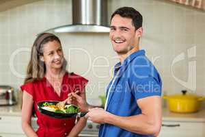 Couple holding pan of vegetables and smiling