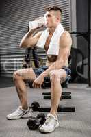 Shirtless man on bench drinking protein shake