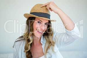 woman wearing a straw fedora smiling into the camera