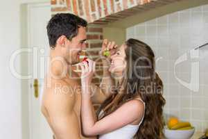 Young couple feeding fruits to each other