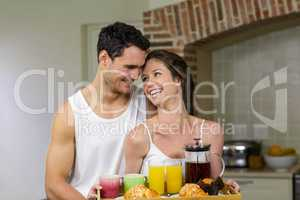Happy couple holding a tray of breakfast