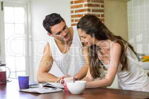 young couple looking their personal organizer in morning