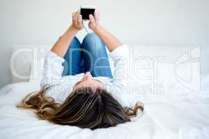 woman lying on her bed looking at her phone and listening to mus