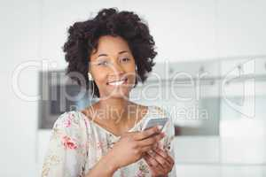 Smiling woman with earphones using smartphone