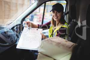 Delivery woman holding clipboard to camera