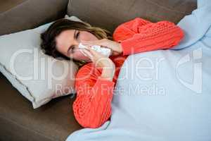 sick woman blowing her nose into a tissue