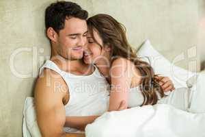 Young couple cuddling on bed