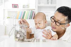 Father and baby saving money