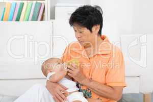 Nanny bottle feeding baby