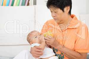 Babysitter bottle feeding baby