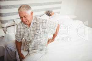 Senior man suffering from backache sitting on bed