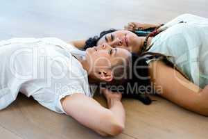 Lesbian couple lying on wooden floor