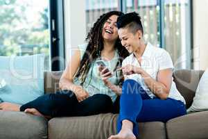 Lesbian couple looking at mobile phone and smiling
