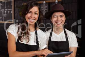 Smiling co-workers using tablet