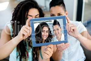 Lesbian couple taking a selfie with digital tablet