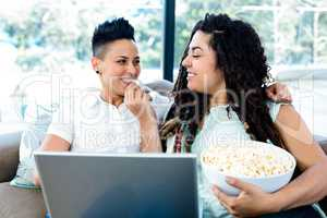 Woman feeding popcorn to her partner while using laptop
