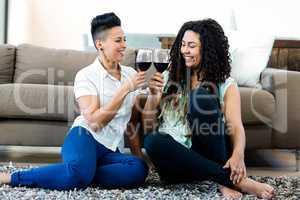 Lesbian couple toasting wine glasses