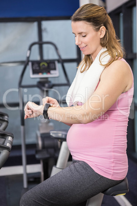 Pregnant woman on exercise bike using smartwatch