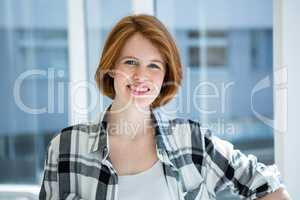 Red haired hipster smiling at camera