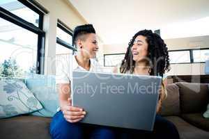 Lesbian couple smiling while using laptop