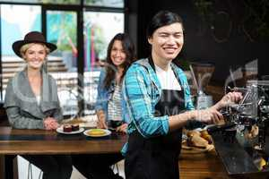 Smiling waiter in apron behind the counter