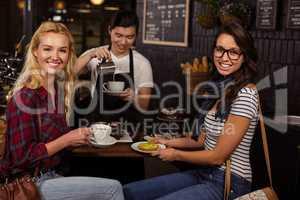 Smiling friends enjoying pastries
