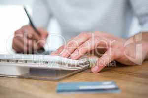 Masculine hands taking notes and typing on keyboard