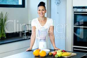 Pregnant woman standing near worktop with blender and fruits