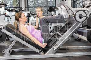 Trainer motivating pregnant woman while using leg press