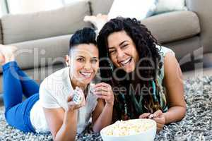 Lesbian couple lying on rug and watching television