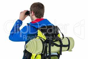 Side view of backpacker looking through binoculars