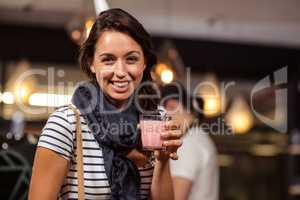 Smiling brunette drinking a beverage