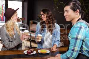Smiling friends enjoying coffee and pastries