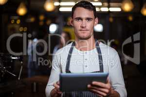 Barista holding tablet and looking at the camera