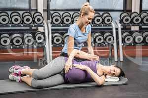 Smiling trainer manipulating pregnant woman