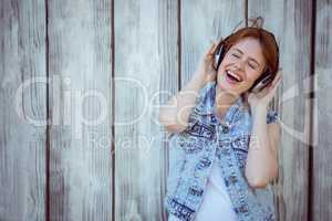 smiling hipster woman listening to loud music through headphones