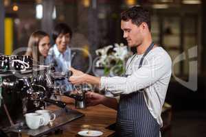 Barista making hot milk with coffee machine